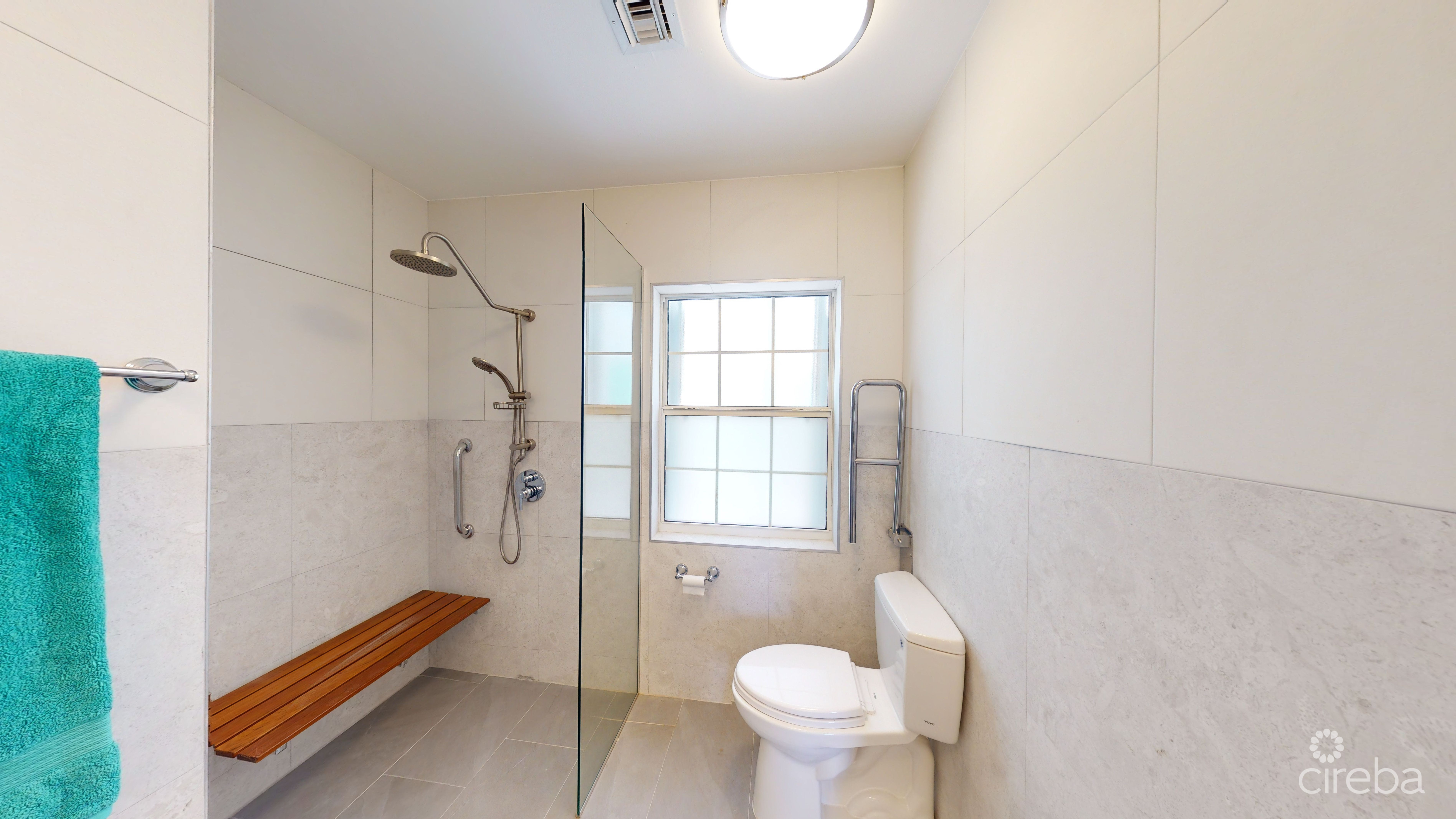 ADA wheelchair accessible shower  with folding shower seat,  and handles on both sides. Folding arm handle beside the toilet as well. Tiled floor to ceiling.